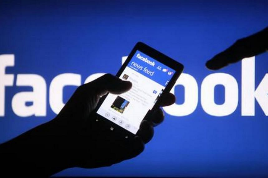 A smartphone user shows the Facebook application on his phone in the central Bosnian town of Zenica, in this file photo illustration taken on May 2, 2013.
