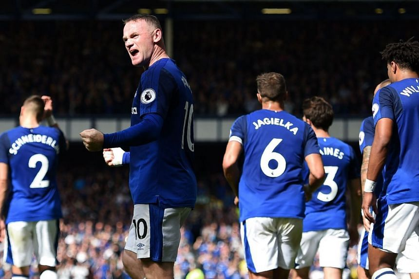 Everton's English striker Wayne Rooney (centre) and teammates celebrate a goal.