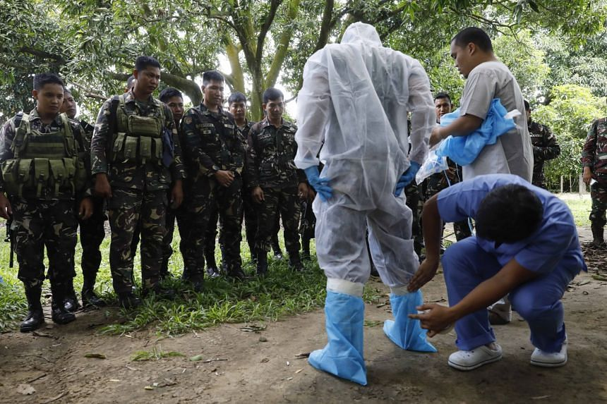 A Philippine Army soldier is dressed in protective clothing by two veterinarians at a designated command center for health, animal and agriculture authorities on Aug 17, 2017.