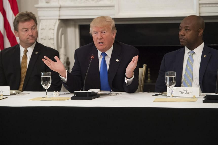 US President Donald Trump speaking alongside US Senator Dean Heller (left), Republican of Nevada, and US Senator Tim Scott (right), Republican of South Carolina, during a meeting with Republican Senators to discuss the health care bill, on July 19, 2