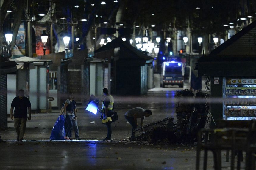 Policemen check the area after towing away the van which ploughed into the crowd, killing at least 13 people and injuring around 100 others on the Rambla in Barcelona, on Aug 18, 2017.