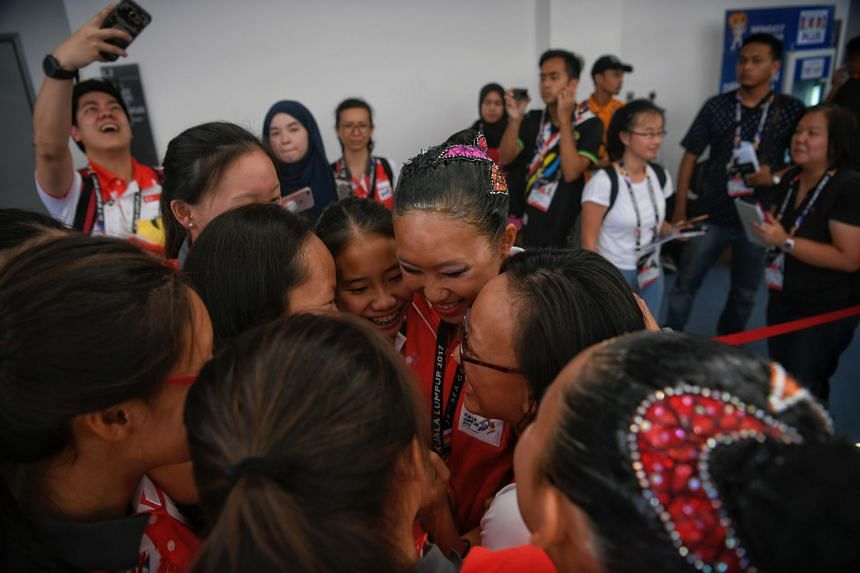 Singapore synchronised swimmer Debbie Soh (centre) celebrates with her team-mates after the medal ceremony for the solo free routine event. The 19-year-old clinched Singapore's first gold medal at this SEA Games yesterday afternoon, and then added a