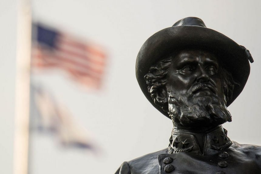 """The American Flag flies behind a statue of Confederate General Thomas """"Stonewall"""" Jackson, in Charleston, West Virginia."""