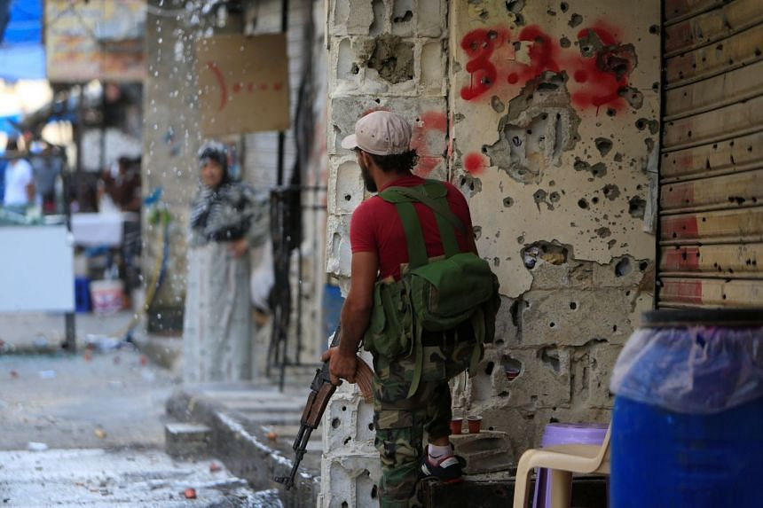 A member of the joint Palestinian security force stands in front of a bullet-riddled wall inside the Ain el-Hilweh refugee camp.