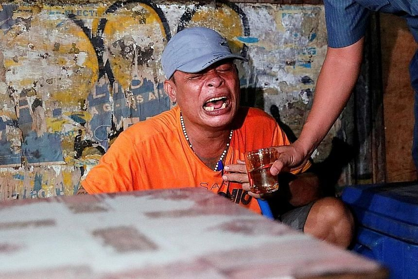 A man mourning the death of his brother, who police say was killed in a spate of drug-related violence in Manila on Wednesday.