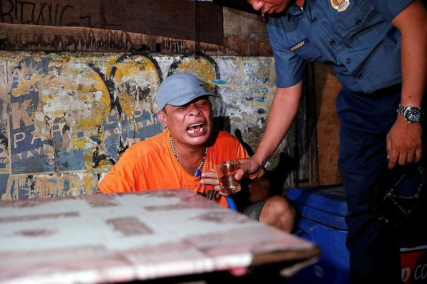 A cop offering water to a man as he comforts him after his brother was killed in a spate of drug-related violence in Manila. About 3,200 alleged drug suspects have been killed in purported gunbattles with police.