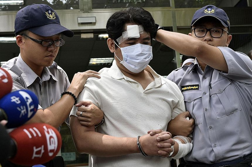 The suspect being escorted by policemen at a local police bureau in Taipei yesterday. A military police guard was slashed on the neck by the attacker who was carrying the national flag of China.