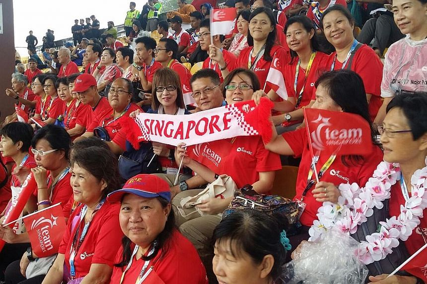 Team Singapore supporters watching the football match between Singapore and Laos yesterday. They are on the ActiveSG Experience Tour.
