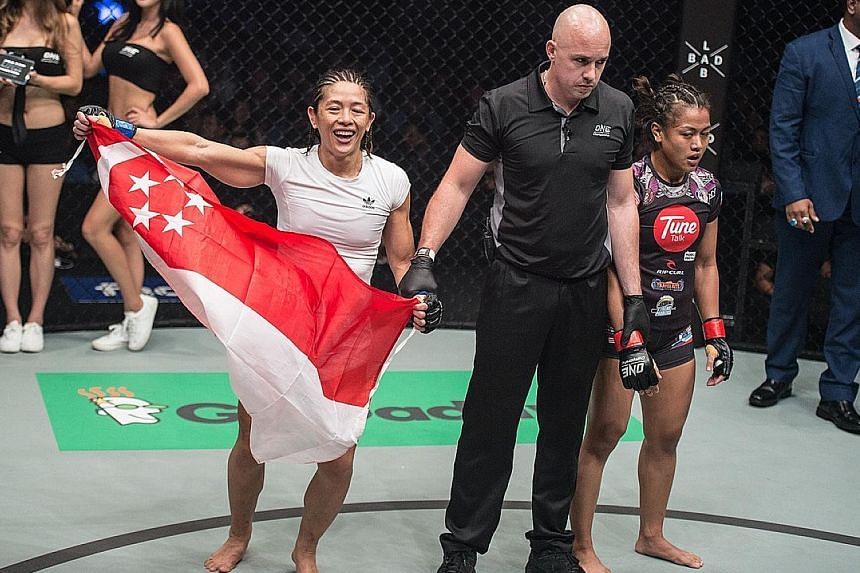 May Ooi holds up the Singapore flag after beating home favourite Ann Osman at One Championship's Quest for Greatness event at the Stadium Negara in Kuala Lumpur.