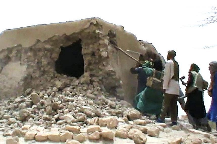 Left: The 15th-century mosque in Mali that was destroyed has been restored with the help of foreign donors. Above: A still from a video taken on July 1, 2012, showing Islamist militants destroying one of the nine shrines.
