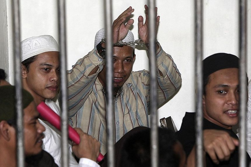 ISIS-linked cleric Aman Abdurrahman (hands raised) in a holding cell in Jakarta awaiting trial in 2010. He was given special remission from his 10-year jail sentence as part of Indonesia's 72nd Independence Day celebrations on Thursday, but was taken