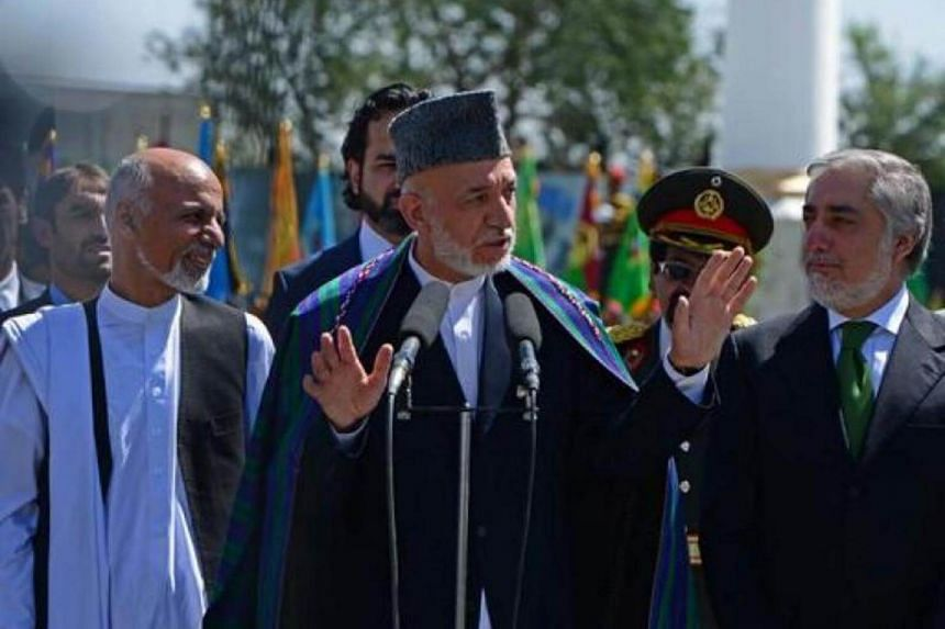 Afghan President Hamid Karzai (centre) gestures while speaking as presidential candidates Ashraf Ghani (left) and Abdullah Abdullah look on during an event to mark Independence Day at the Ministry of Defence compound in Kabul on Aug 19, 2014.