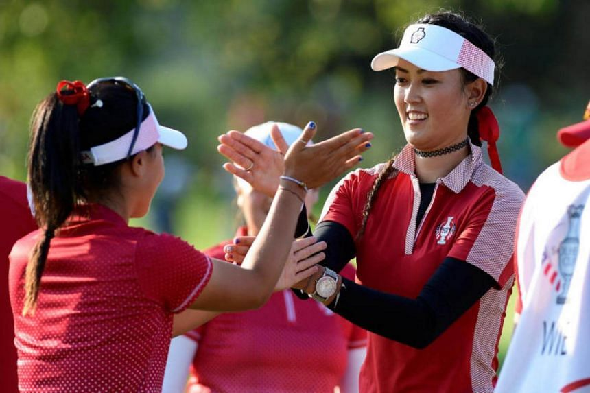 USA players Danielle Kang (left) and Michelle Wie celebrate after winning their Friday (Aug 18, 2017) afternoon match during The Solheim Cup international golf tournament at the Des Moines Golf and Country Club.