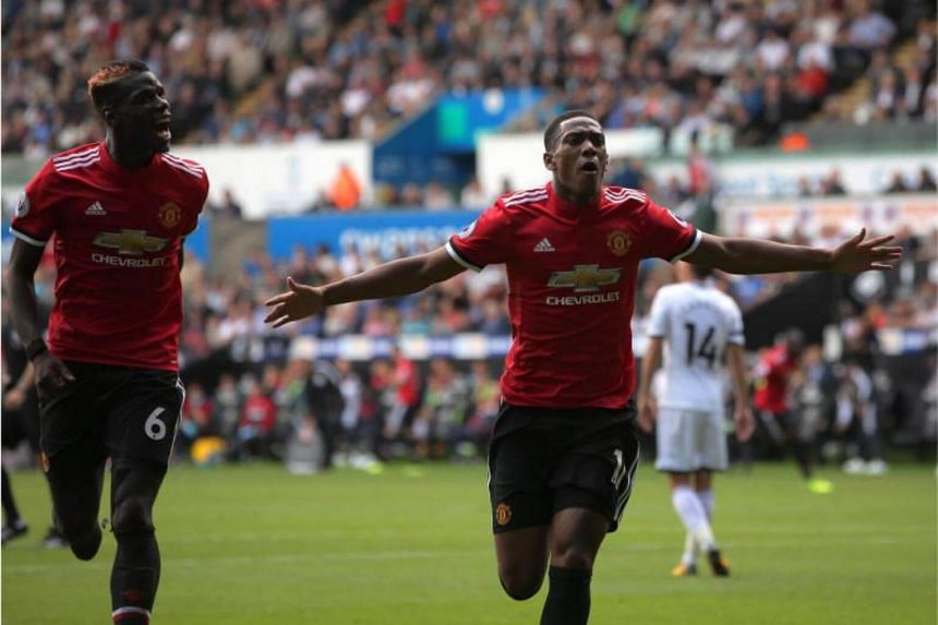 Anthony Martial of Manchester United (right) celebrates his goal with co-scorer Paul Pogba making the score 0-4 during the English Premier League soccer match between Swansea City and Manchester United at Liberty Stadium, Swansea, Britain on Aug 19,