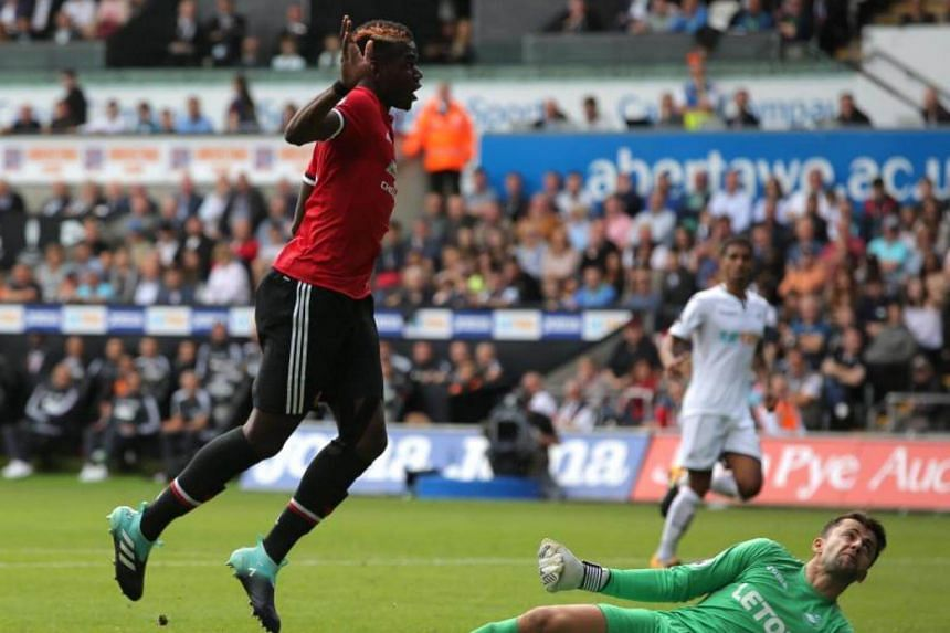 Paul Pogba of Manchester United scores a goal against Lukasz Fabianski of Swansea City (right) making the score 0-3 during the English Premier League soccer match between Swansea City and Manchester United at Liberty Stadium, Swansea, Britain on Aug