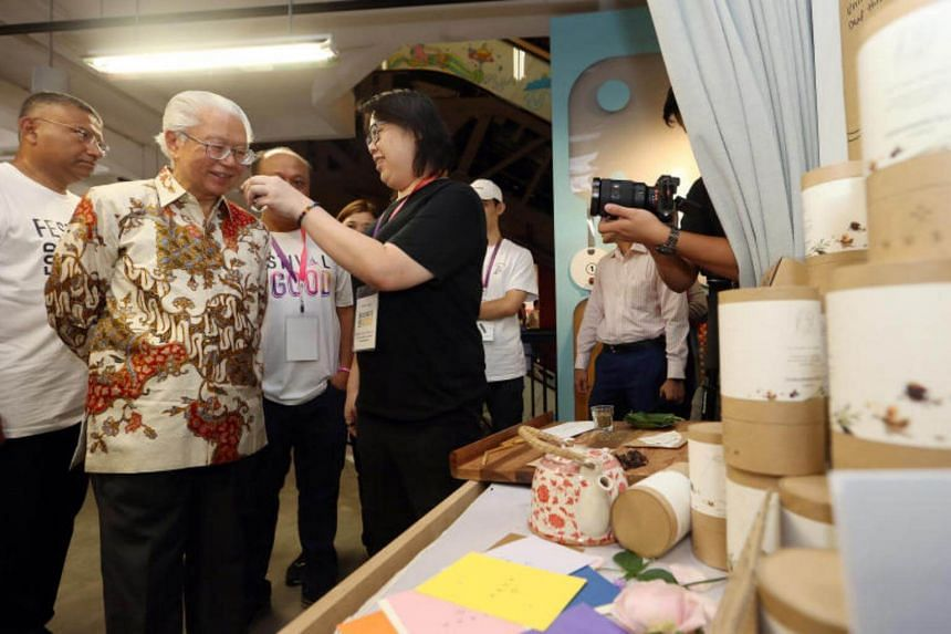Chua Ning Pei, 38 (COO of HUSH) offers the scent of home-made tea ingredients to President Tony Tan Keng Yam at the opening of the FestivalForGood 2017, at lyf@SMU on Aug 19, 2017.
