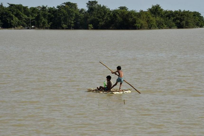 Indian children uses a raft to travel over flood waters in Araria in Bihar state on Aug 19, 2017.