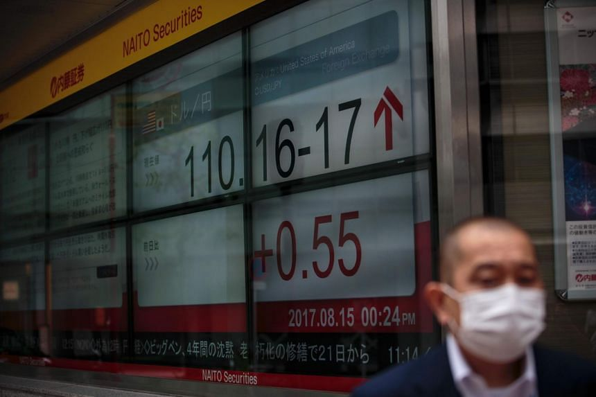 A man walks past a stock quotation board flashing the current foreign exchange rate of the yen against the US dollar in Tokyo, on Aug 15, 2017.