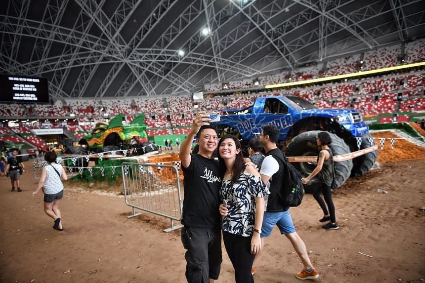 Mr Kenneth Wong, 39 and his wife Kelly Lai, 34 taking a wefie in front of the monster truck, Blue Thunder, on Aug 19, 2017.