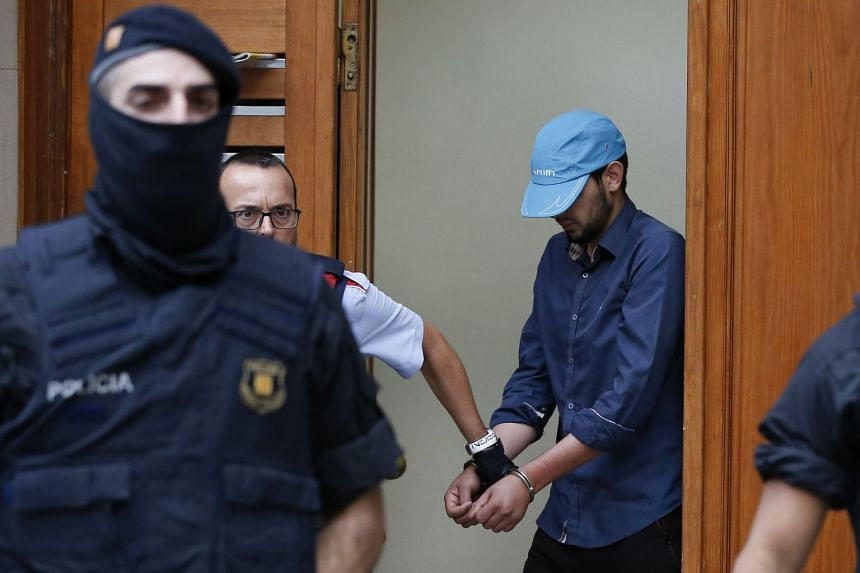 Police detain a cuffed suspect in Ripoll during a search linked to the deadly terror attacks in Barcelona.
