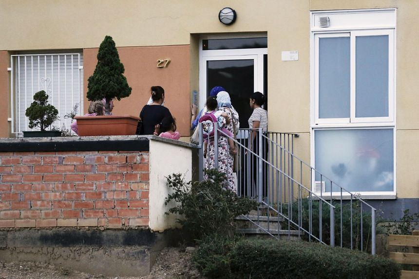 People ring the doorbell of the flat of the Oukabir family in Ripoll.