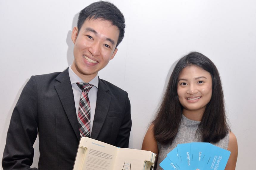 SMU students Ling Kai Tsi and Melissa Chia with a journal and cards that will be used in the Pathfinders programme.