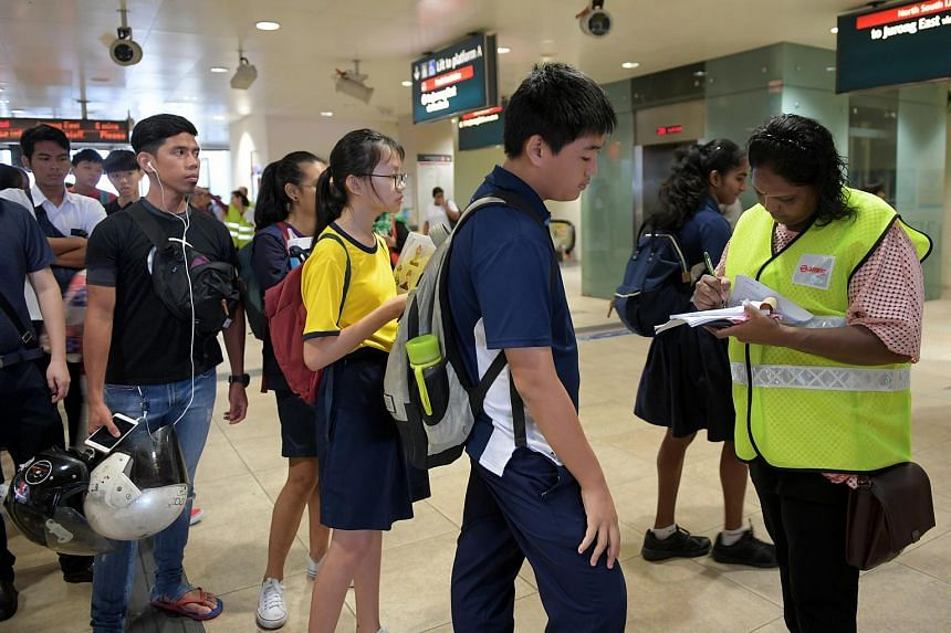 Commuters lining up to get travel chit from SMRT staff at Bishan MRT station.