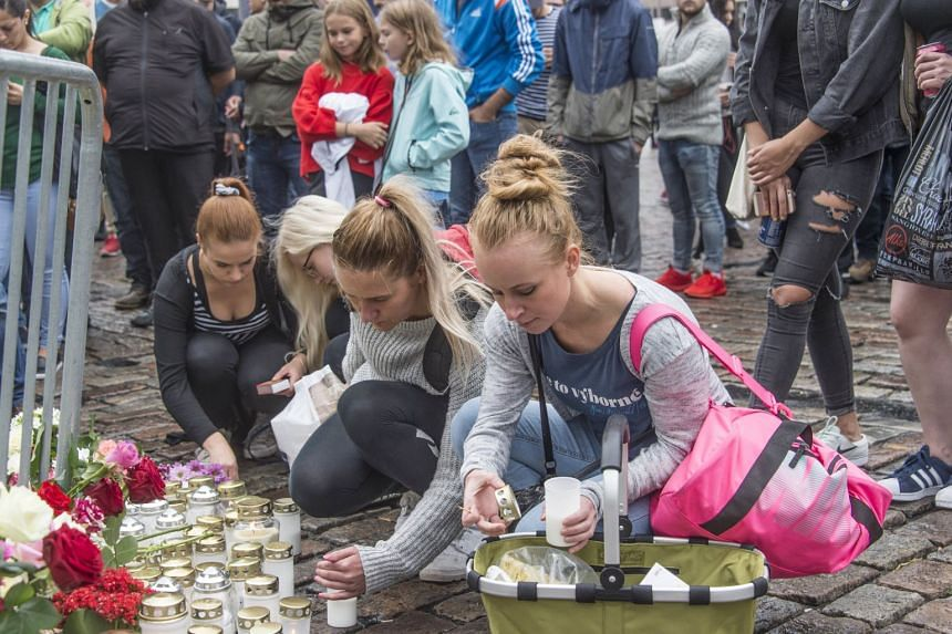 People place candles and flowers at the scene of the attack in Turku, Finland, Aug 19, 2017.