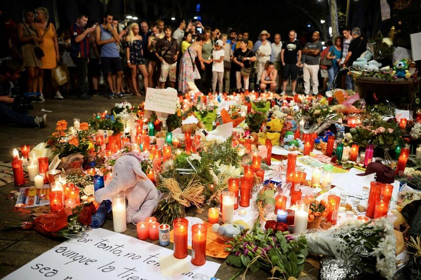 People stand next to flowers, candles and other items set up at the Font de Canaletes in Barcelona on Aug 18, 2017.