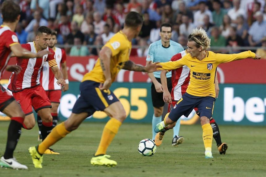 Atletico de Madrid's French forward Antoine Griezmann (right) controls the ball during the Spanish league football match Girona FC vs Club Atletico de Madrid at the Montilivi stadium in Girona on Aug 19, 2017.