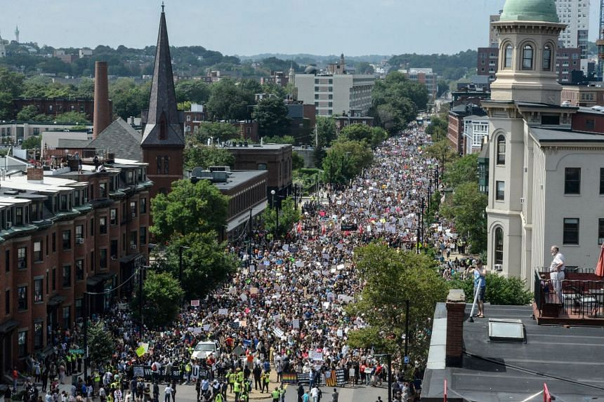 A large crowd of people march towards the Boston Commons to protest the Boston Free Speech Rally.