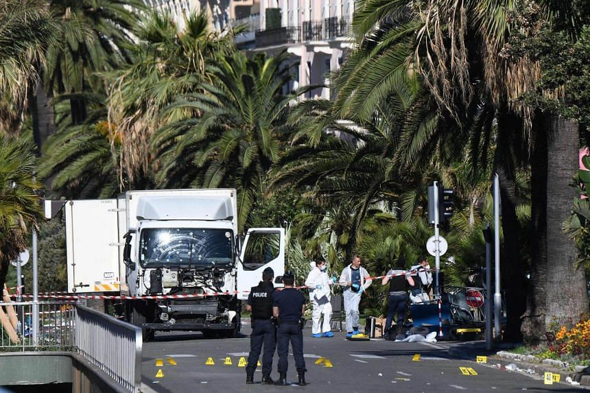 Forensic officers and policemen looking for evidence near a truck on the Promenade des Anglais seafront in the French Riviera town of Nice, after it drove into a crowd watching a fireworks display,  on July 15, 2016.