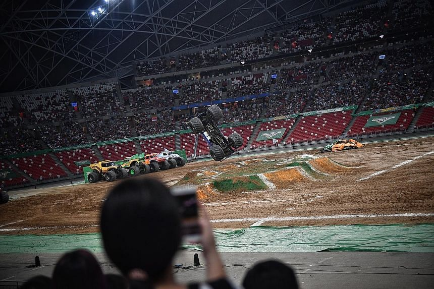 Fans (left) being thrilled by jaw-dropping feats (far left) at Monster Jam Singapore yesterday at the National Stadium. Drivers carried out jumps, doughnuts (where the truck spins in circles) and flip-overs, with the truck's roof on the ground.