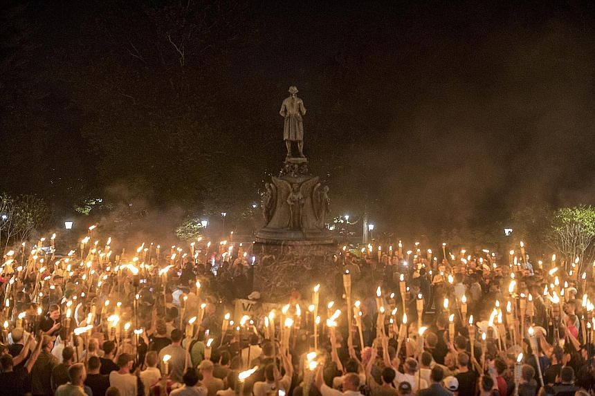 Torch-bearing white nationalists rallying around a statue of Thomas Jefferson near the University of Virginia campus in Charlottesville on Aug 11. The white nationalists - unlike neo-Nazis in Europe and Al-Qaeda and ISIS militants who cover their fac