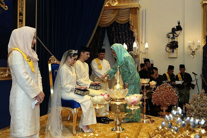 The Queen of Johor, Raja Zarith Sofiah, blessing Princess Tunku Tun Aminah Sultan Ibrahim and Dutch-born Dennis Muhammad Abdullah at their Istiadat Bersanding (sitting-in state ceremony) at the Grand Palace on Monday. Many had wondered about the desi