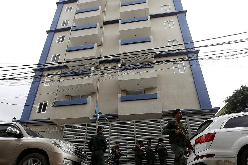 Cambodian police standing outside the building where 225 Chinese nationals were arrested on Wednesday on suspicion of carrying out a telephone and Internet scam on victims in China.