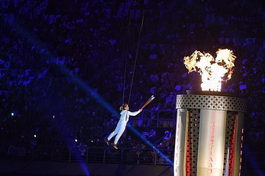 Malaysian diver Nur Dhabitah Sabri being hoisted up in the air to light the cauldron during the SEA Games opening ceremony at the National Stadium in Kuala Lumpur last night. The biennial Games were officially opened by the King of Malaysia, Sultan M
