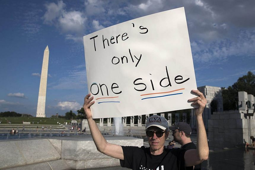 A man holds a sign during a rally of solidarity against violence beside the Lincoln Memorial Reflecting Pool in Washington, on Aug 13, 2017.