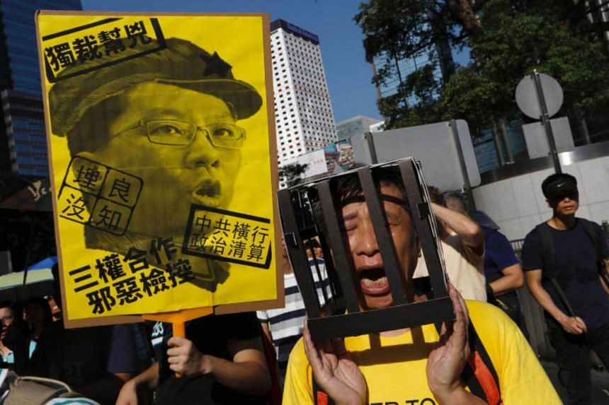 A demonstrator holds cardboard jail bars, as he protests for the jailing of student leaders Joshua Wong, Nathan Law and Alex Chow, who were imprisoned for their participation of the 2014 pro-democracy Umbrella Movement.