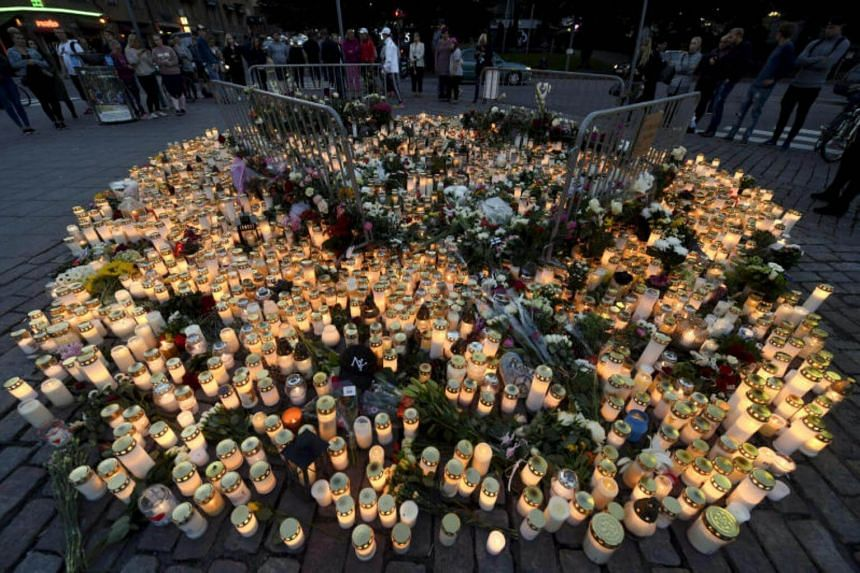 Memorial cards, candles and flowers for the victims of Friday's stabbings are placed on the Market Square in Turku, Finland on Aug 19, 2017.