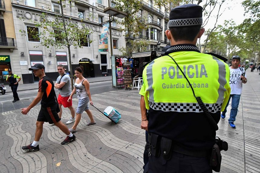 Police officers stand guard on the Las Ramblas boulevard in Barcelona on Aug 19, 2017.