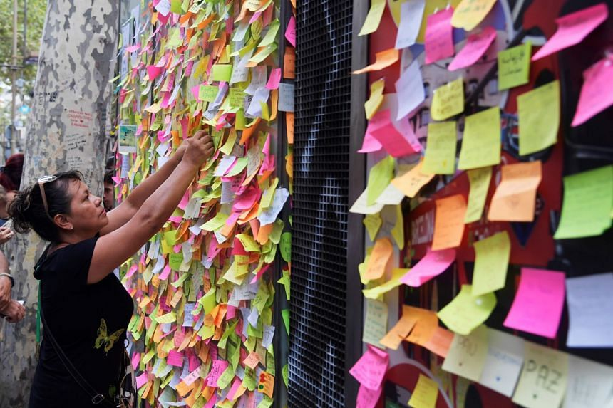 People leave post-it notes with messages against the attacks and in tribute to the victims of the Barcelona attack, on a kiosk on Las Ramblas boulevard in Barcelona on Aug 19, 2017.