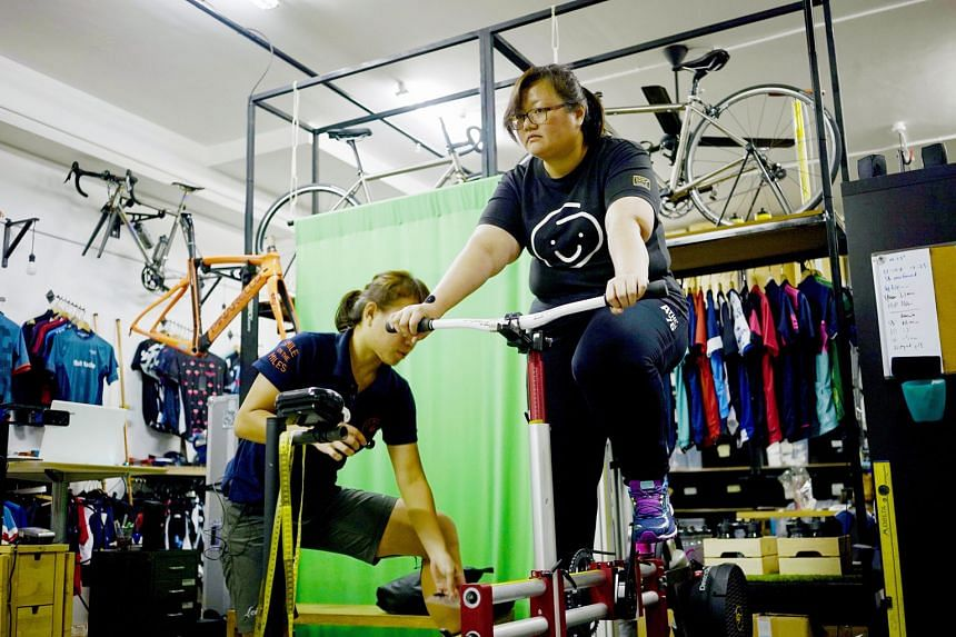 Graphic designer Christine Lim pedalling on a stationary adjustable bicycle jig as Shuwie Chang, sports scientist and bike fitter at Loue Bicycles, makes adjustments after checking her pressure distribution results.