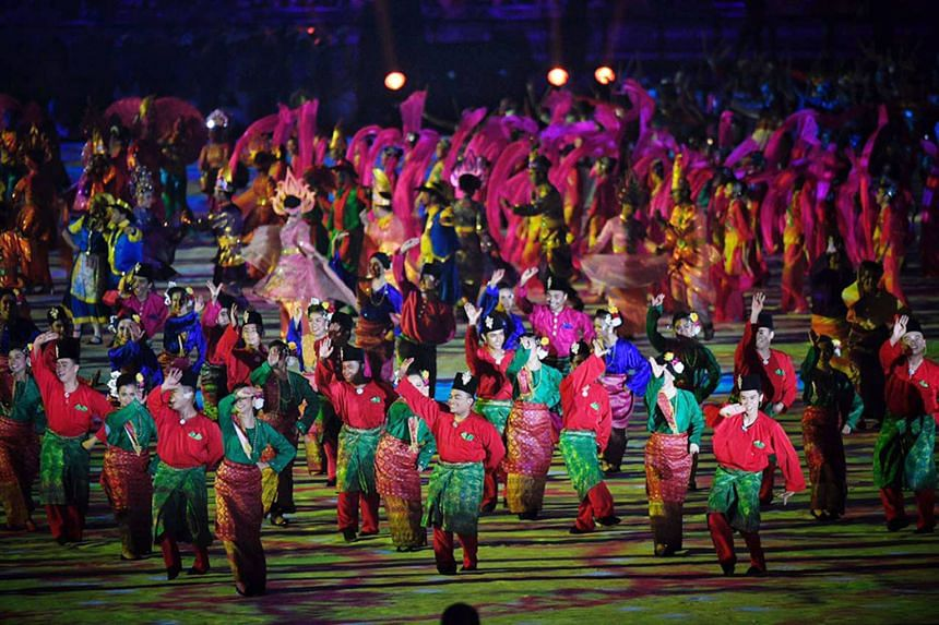Clockwise from top: Fireworks; the performers including wushu exponents and traditional dancers; and the Singapore contingent, led by shooter Jasmine Ser, walking out during the athletes' parade at the Bukit Jalil National Stadium yesterday.