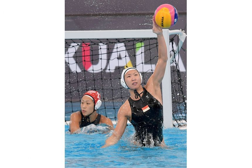 Singapore's Angeline Teo rises to block a shot from Thailand during the SEA Games women's water polo competition at Bukit Jalil's National Aquatic Centre. Teo scored to make it 1-1 before the Thais ran away with a 5-1 win.
