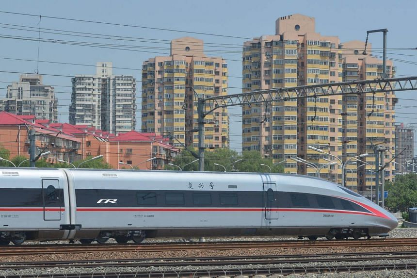 """A new model of China's Electric Multiple Unit (EMU) train """"Fuxing"""" leaves Beijing South Railway Station for Shanghai Hongqiao Railway Station, in Beijing, on June 26, 2017."""
