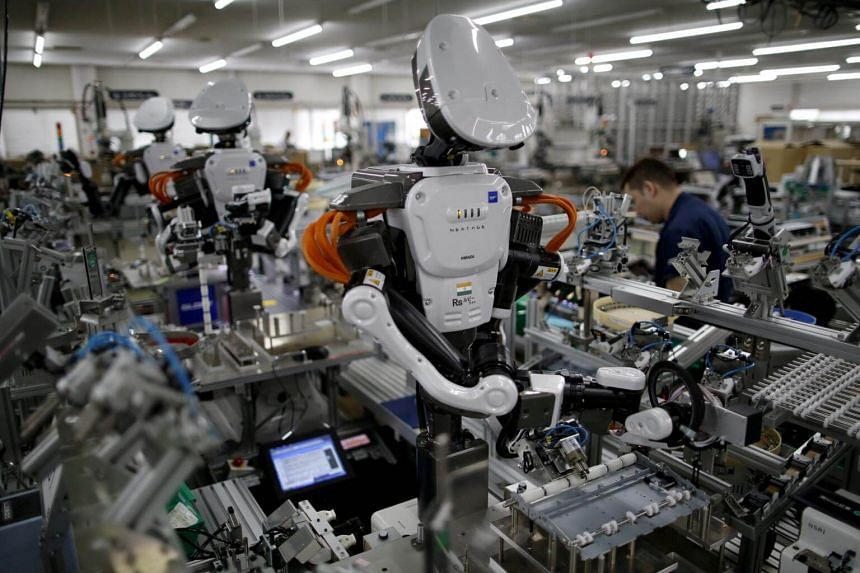 Humanoid robots work side by side with employees in the assembly line at a factory of Glory Ltd., a manufacturer of automatic change dispensers, in Kazo, Japan, on July 1, 2015.