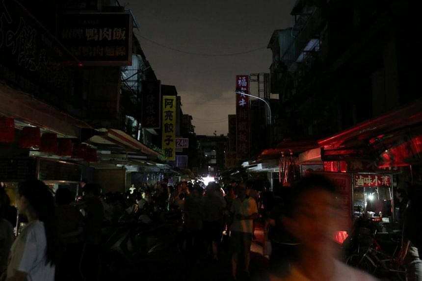 People walking along a street during a massive power outage in Taipei on Aug 15, 2017.