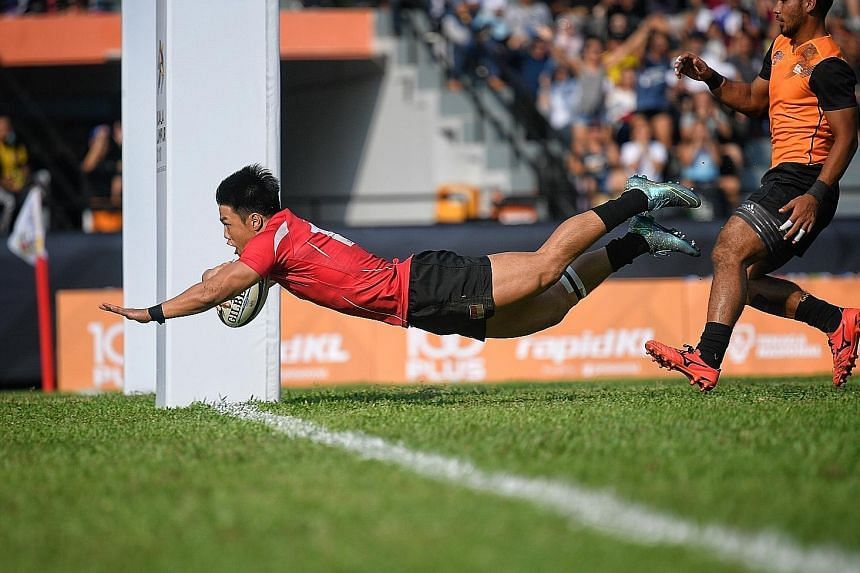 Singapore's Nicholas Yau scoring a fourth-minute try in the rugby sevens final against Malaysia to make it 5-5. The hosts won 22-7.
