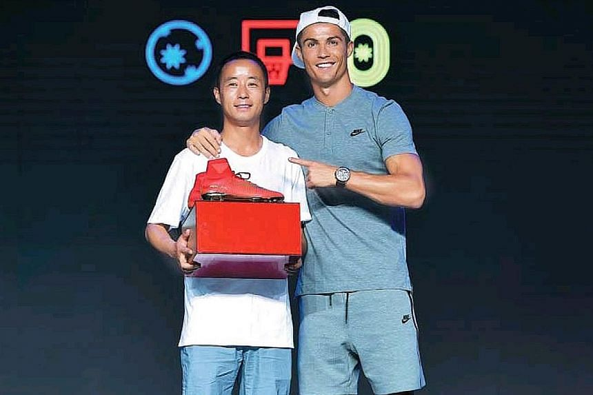 Mr Lyu Shaowu with Cristiano Ronaldo, who gave the primary school teacher a pair of his boots. Mr Lyu's dedication in teaching more than 30 pupils football on a wasteland at his school in Gansu province's Longxi county has drawn focus to his little-k